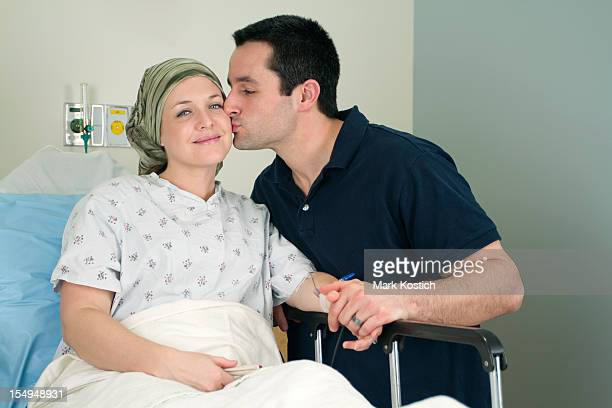 Man giving a kiss to a woman in a hospital bed