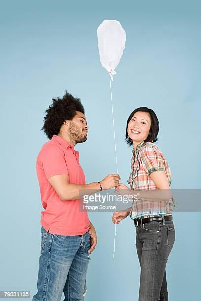 Um homem dando a mulher uma mala balão