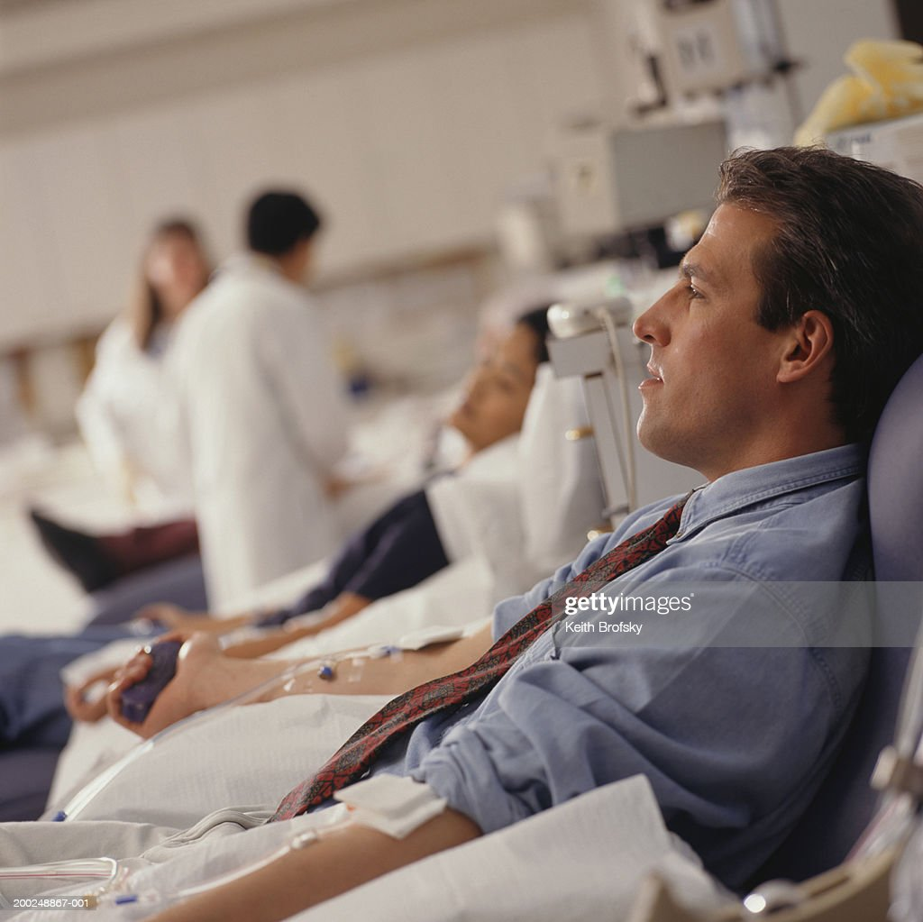 Man giving blood in hospital : Stock Photo
