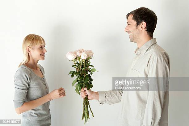 Man Giving Bouquet To Young Woman