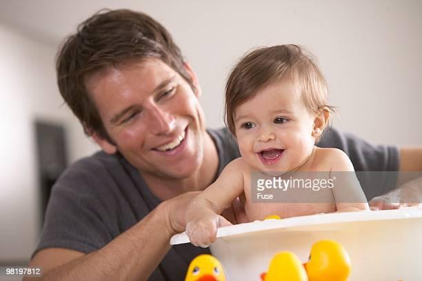 Man giving child a bath