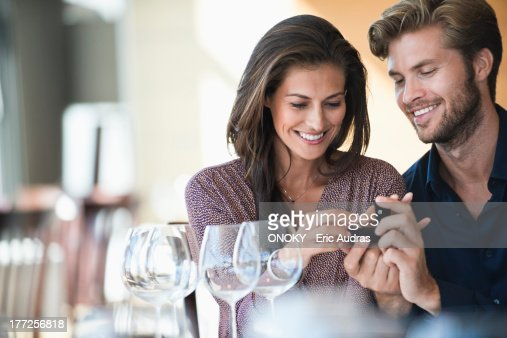 Man giving engagement ring to his girlfriend in a restaurant : Foto de stock