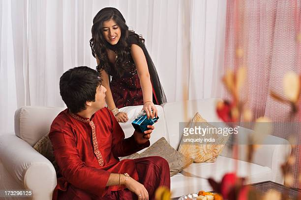Man giving gift to his sister at Raksha Bandhan