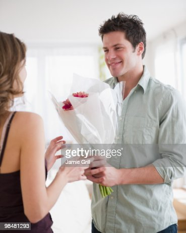 Man giving girlfriend bouquet of flowers  : Stock Photo
