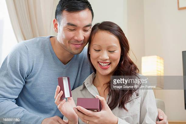 Man giving girlfriend gift on sofa