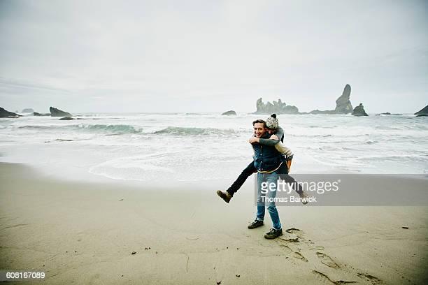 Man giving girlfriend piggyback ride on beach