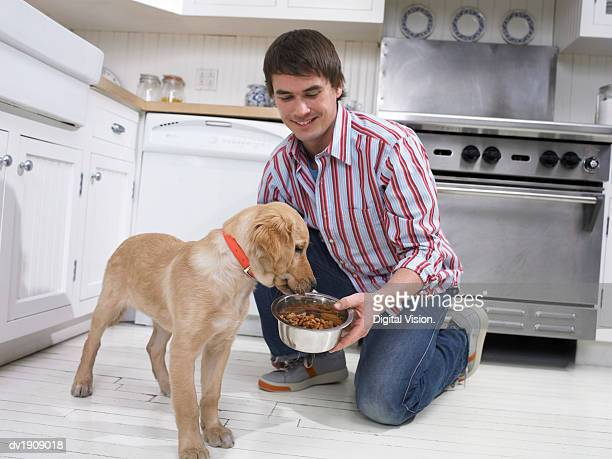 Man Giving His Dog a Bowl of Food