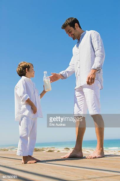 Man giving milk bottle to his son on the beach