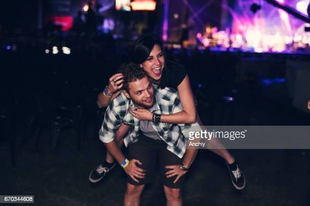 Man giving piggy back to his friend in front of the stage