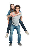 Portrait Of Young Man Piggybacking Her Girlfriend Isolated On White Background