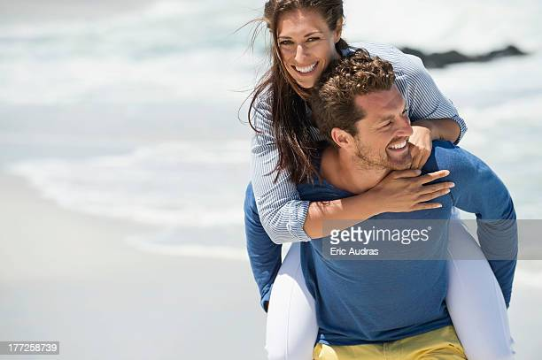 Man giving piggyback ride to his wife on the beach