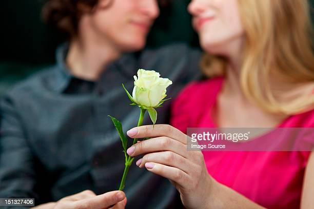 Man giving rose to woman