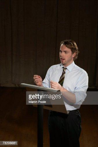 Man giving speech at podium : Stock Photo