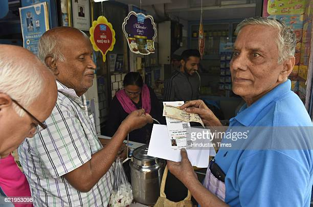 A man giving the photocopy of Aadhar Card along with Rs 1000 at a Mother Dairy milk booth in Mayur Vihar on November 9 2016 in New Delhi India In a...