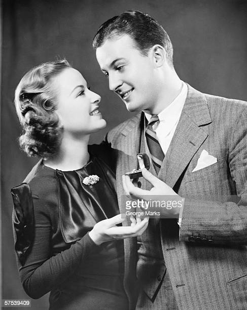 Man giving to fiance engagement ring in studio, (B&W), portrait