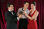 Man giving trophy to smiling couple