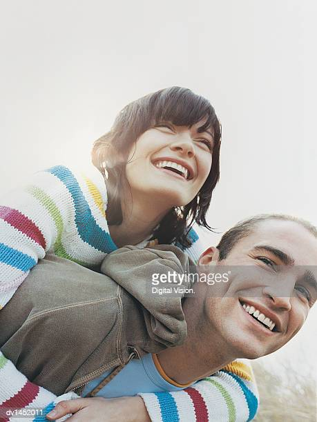 Man Giving Woman a Piggyback Laughing
