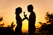 Man giving woman a rose. (romance and dating concepts)