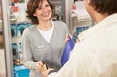 Man giving woman card at shop counter, smiling, close up