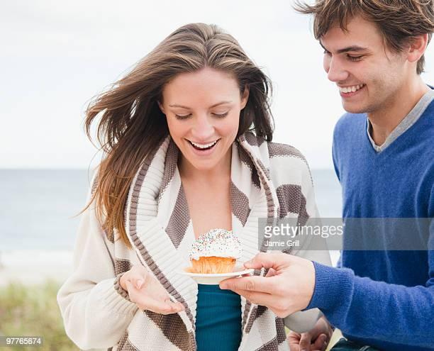 Man giving woman cupcake