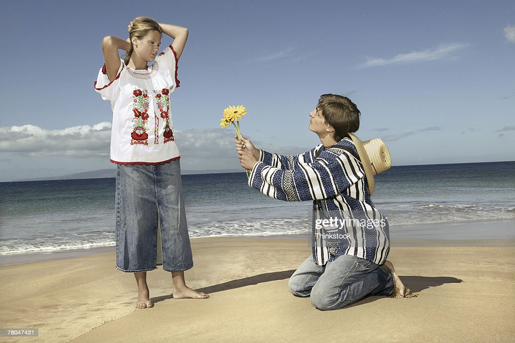 Man giving woman flower at beach : Stock Photo
