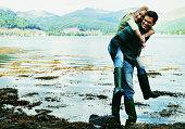 Man Giving Woman Holding a Bucket a Piggyback Beside a Lake