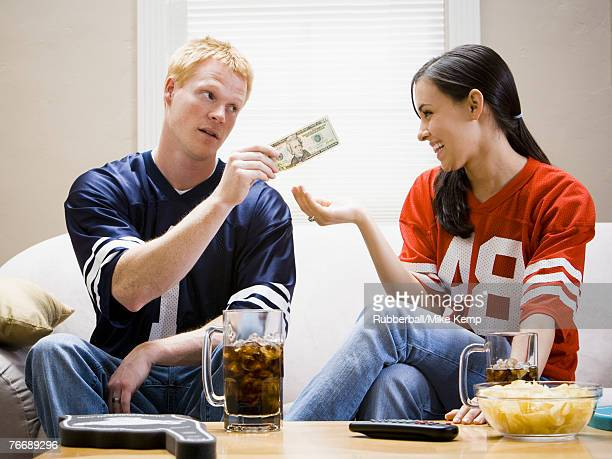 Man giving woman money both in football jerseys