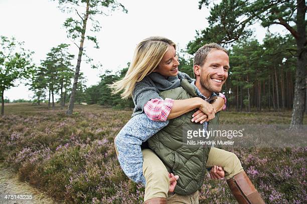 Man giving woman piggy back