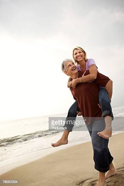 Man giving woman piggyback ride on beach