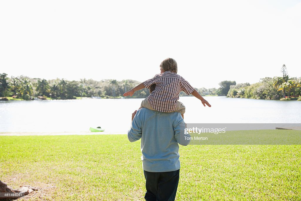 Man giving young boy shoulder ride outdoors at park by a lake : Stock Photo