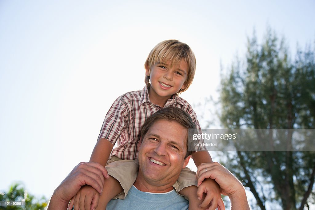 Man giving young boy shoulder ride outdoors at park : Stock Photo