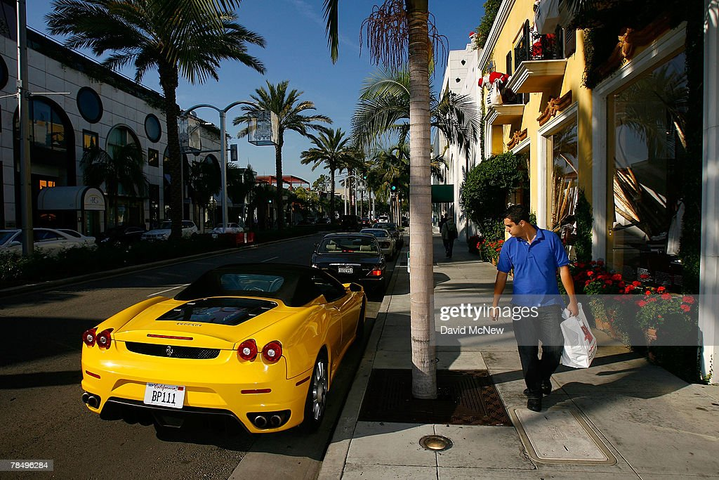 A man glances at a Ferrari sports car while visiting businesses that cater to highend luxury item consumers along Rodeo Drive on December 14 2007 in...