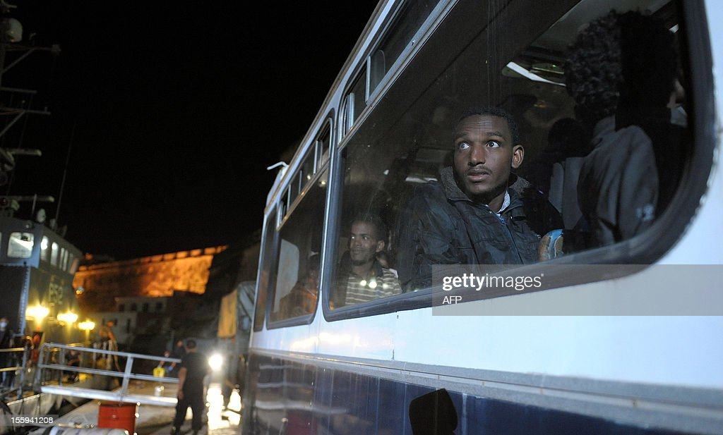 A man glances out of the window of a police bus after disembarking from a patrol boat following a rescue operation upon arrival to the Armed forces of Malta Maritime base of Haywharf, on November 9, 2012 in Valletta. The Maltese military rescued 250 undocumented migrants believed to be Eritrean from a stricken boat, officials said, after reports the vessel had been adrift for days. AFP PHOTO/Matthew Mirabelli -MALTA