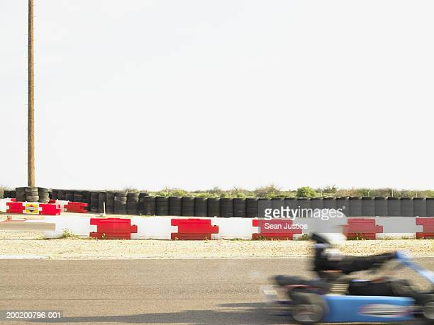 Man go-cart racing on track, side view (blurred motion)