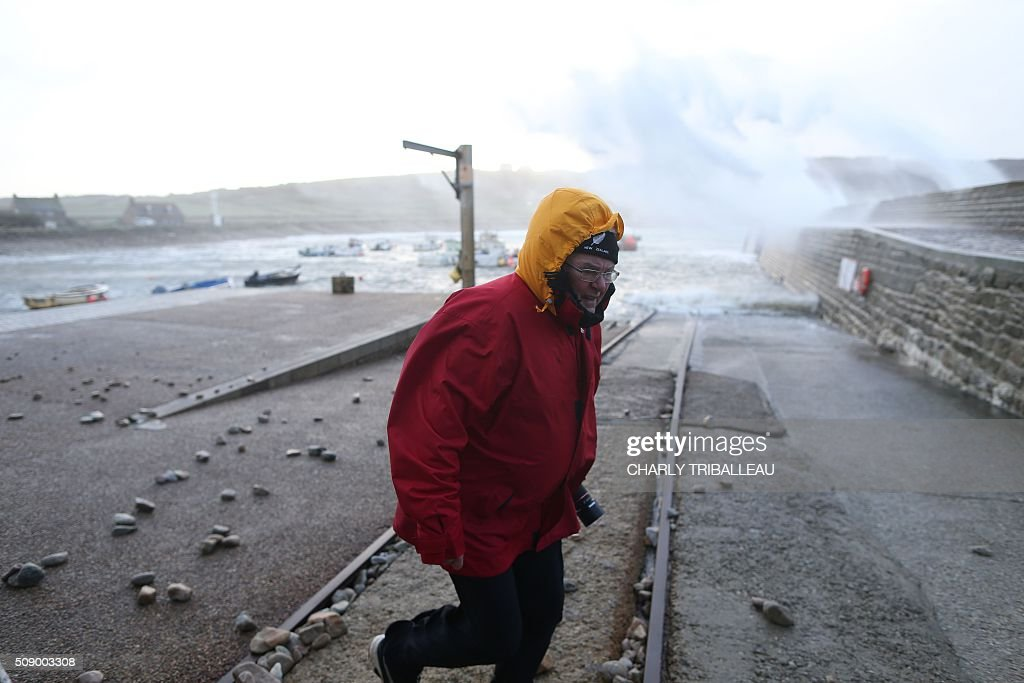 A man goes for a walk in the harbour of Auderville, northwestern France, on February 8, 2016, as strong winds hit the region. Winds of over 130 kh/h were recorded in the region where 16 departments have been placed under alert for wind and flooding waves. / AFP / CHARLY TRIBALLEAU