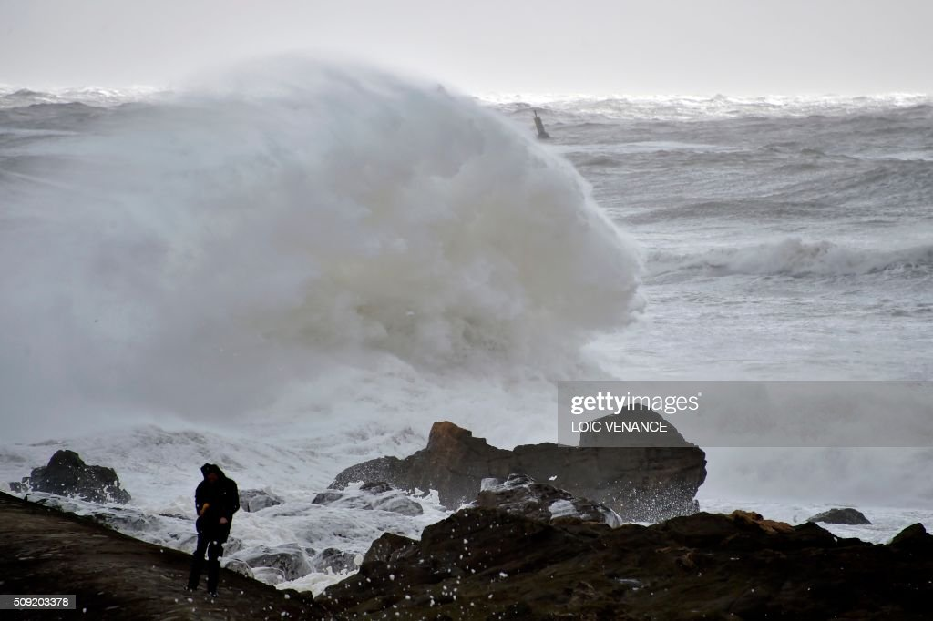 A man goes for walk as waves break in Les Sables-d'Olonne, western France, on February 9, 2016. High winds buffeted northwestern Europe on February 8, leaving one woman in France in a coma after she was hit by an advertising hoarding. Electricity was cut to 5,000 homes in northern France. / AFP / LOIC VENANCE