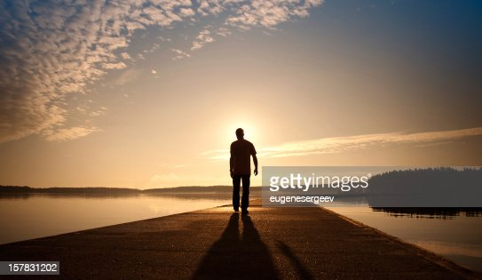 Man goes on concrete pier in the sunrise : Stock Photo