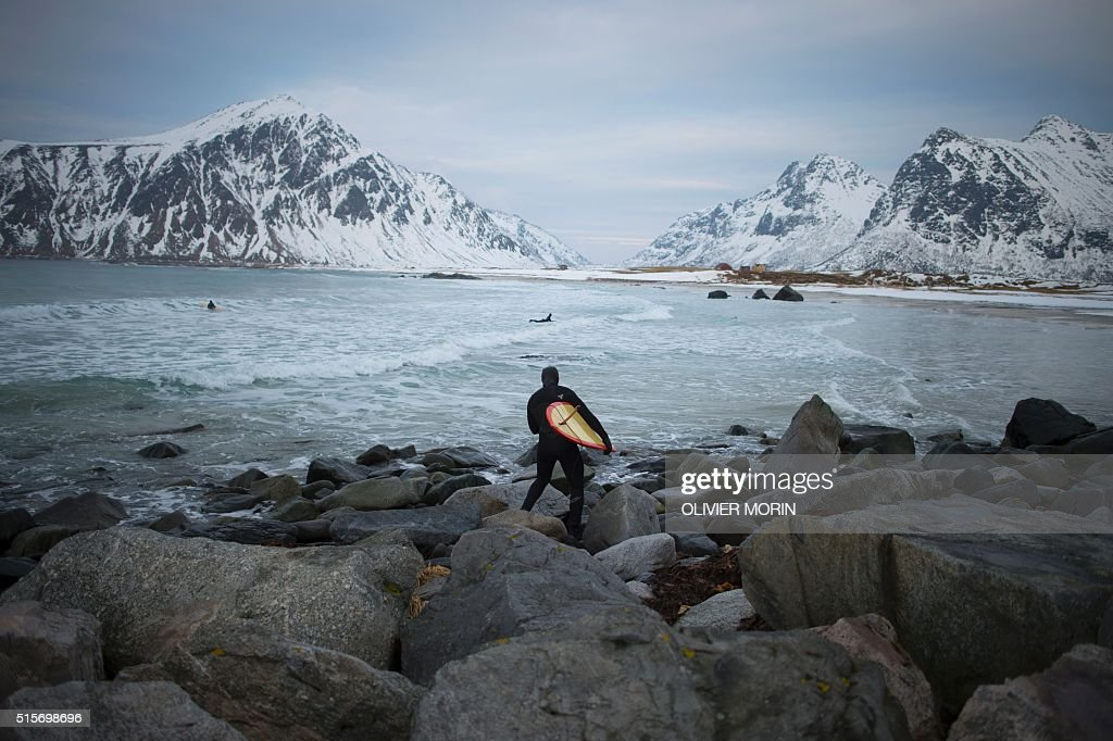 A man goes to surf at the snowy beach of Flackstad, near Ramberg, in Lofoten archipelago, Arctic Circle, on March 12, 2016. Surfers from all over the world come to Lofoten islands to surf in extrem conditions. Ocean temperature is 5-6 °C, air temperature around 0°C in spite of a weather very unstable. / AFP / OLIVIER