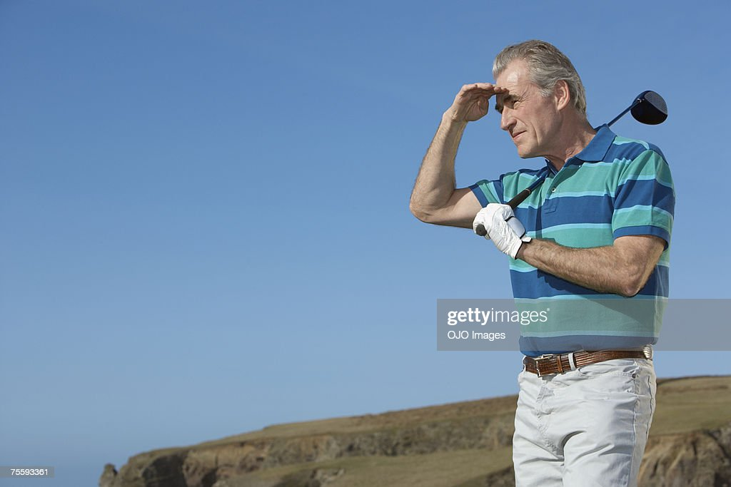 Man golfing trying to see where his drive went : Stock Photo