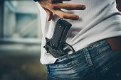 Man grabbing quickly a pistol, hands close up