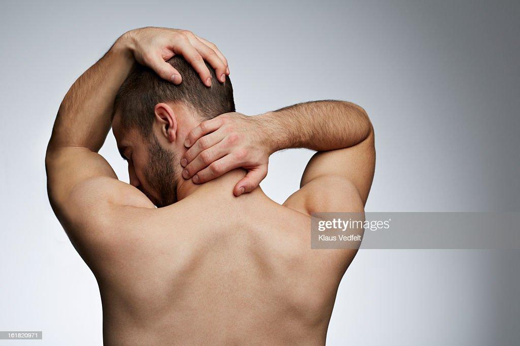 Man grabbing neck & head because of pain : Stock Photo
