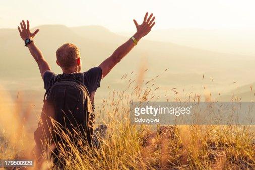 Man greeting golden rising of the sun : Stock Photo
