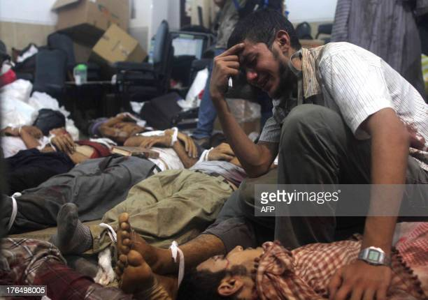 A man grieves as he looks at one of many bodies laid out in a make shift morgue after Egyptian security forces stormed two huge protest camps at the...