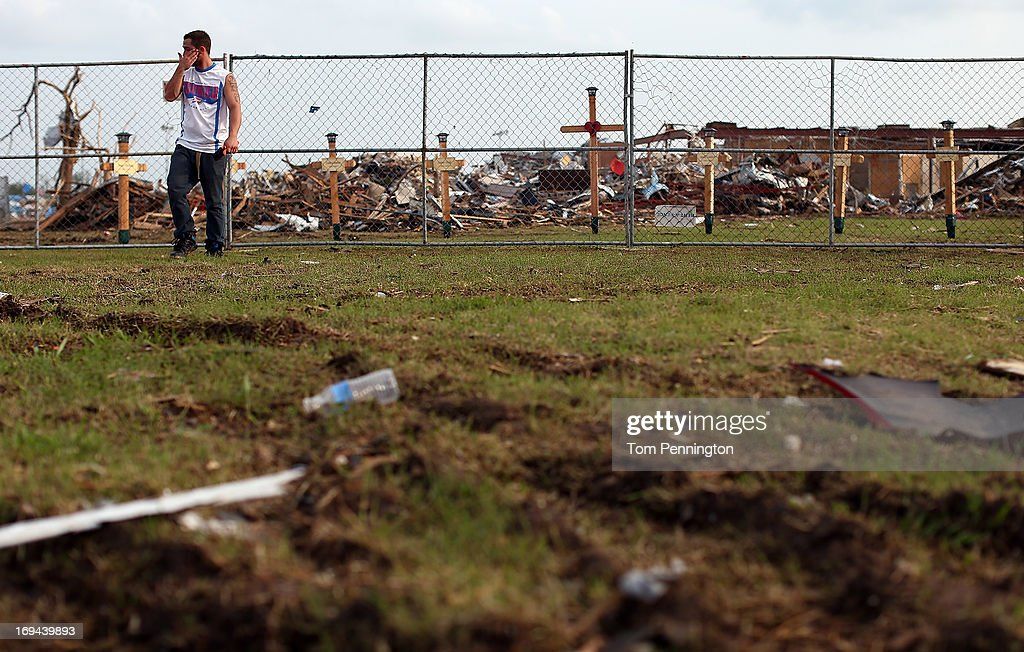 A man grieves while visiting a makeshift memorial at Plaza Towers Elementary School on May 24, 2013 in Moore, Oklahoma. Seven children from the school lost their lives in the storm. The tornado of at EF5 strength and two miles wide touched down May 20 killing at least 24 people and leaving behind extensive damage to homes and businesses. U.S. President Barack Obama promised federal aid to supplement state and local recovery efforts.