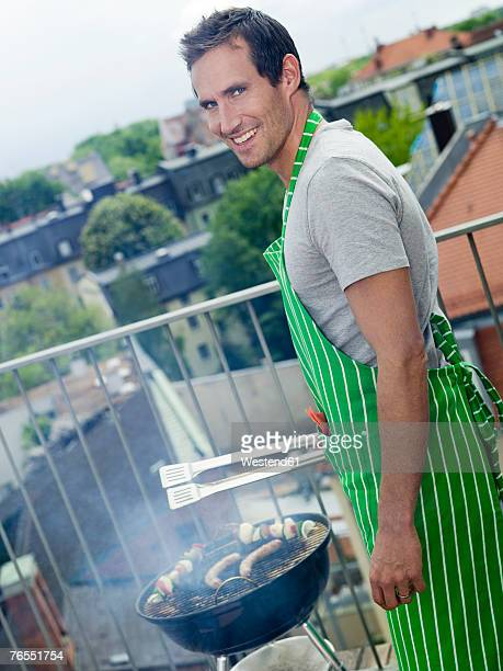 Man grilling outdoors, smiling