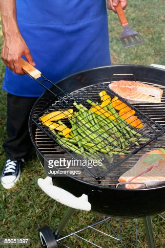Man grilling salmon , asparagus and bell pepper