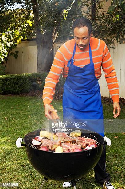 Man grilling steaks and vegetables