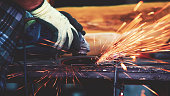 Man is grinding parts that he has just welded together. He is going around all parts of that weld, to have smooth surface. Sparks form grinder goes all around. On the table he has welding tool, and an
