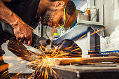 A young man welder a brunette in a black T-shirt and safety goggles. He processes a metal item from a angle grinder in the workshop. Close-up on the sides fly sparks from the  a angle grinder