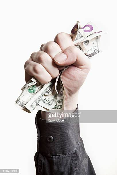 A man gripping a wad of US paper currency, close-up of hand